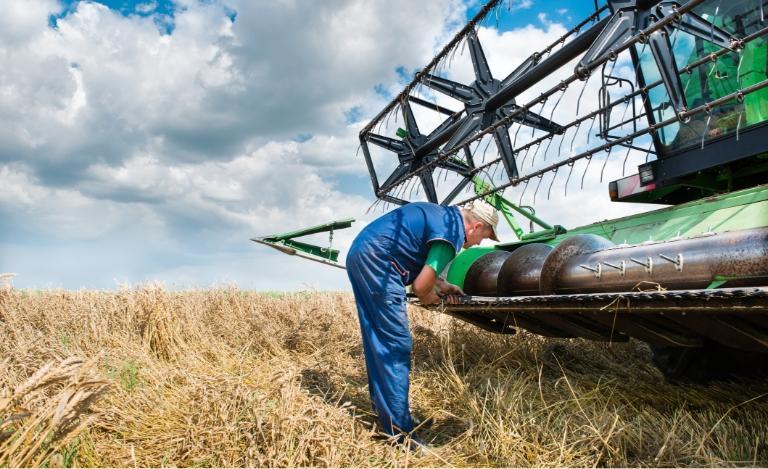 Rolnik pracujący przy kombajnie